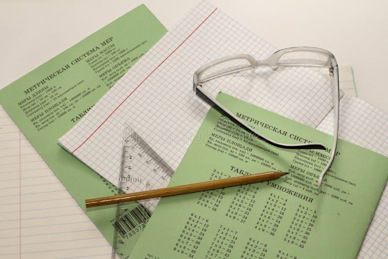 Anteckningsböcker, blyertspennan, radergummit och linjalen är på en vit bakgrund arkivfoto