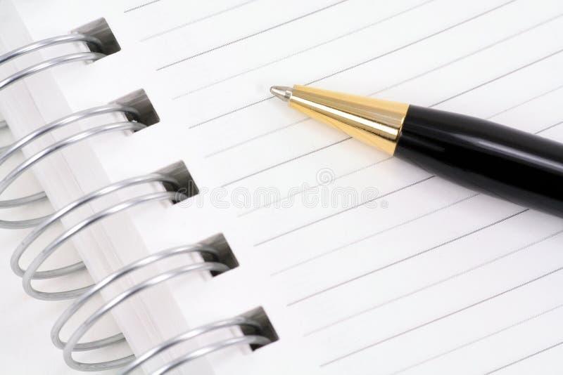 anteckningsbok öppnad penna arkivfoto