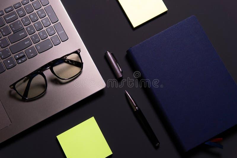 Anteckningsbok, bärbar dator, exponeringsglas och penna på tabellen royaltyfri bild