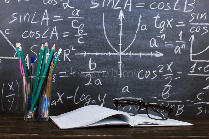 Anteckningsbok, exponeringsglas och ett exponeringsglas med blyertspennor p? svart tavlabakgrund med formler Teacher' s-dagb arkivfoton