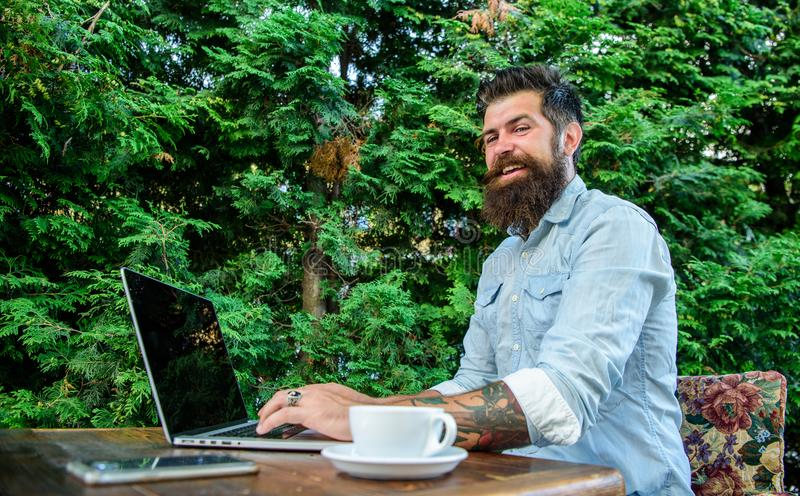 Anteckningsbok för blogg för Hipsterfreelancerarbete online- Bloggeren skapar stolpen, medan tyck om kaffe Mannen uppsökte affärs royaltyfria foton