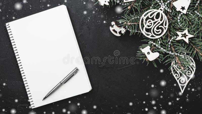 Anteckningsbok för julanmärkningar på svart stenbakgrund Granträd som dekoreras med träleksaker Top beskådar royaltyfria foton