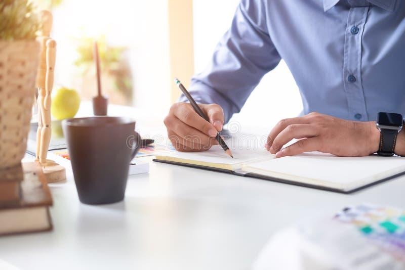 Anteckningsbok för papper för handstil för konstnärman arbetande på den idérika tabellen royaltyfria bilder