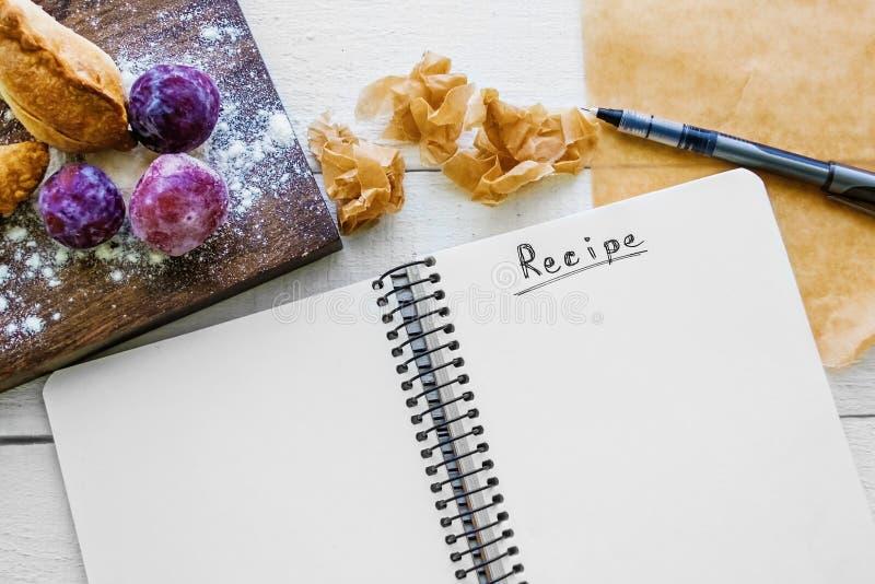 Anteckningsbok för recept med det tomma stället för text, dunsar och pajer fotografering för bildbyråer