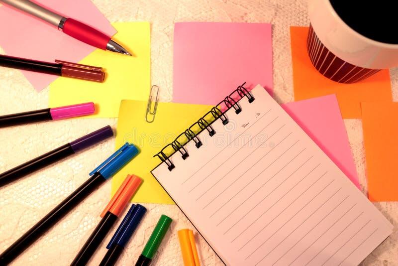 Anteckningsbok, filtpennor i olika färger, klibbiga anmärkningar och en kopp kaffe arkivfoton