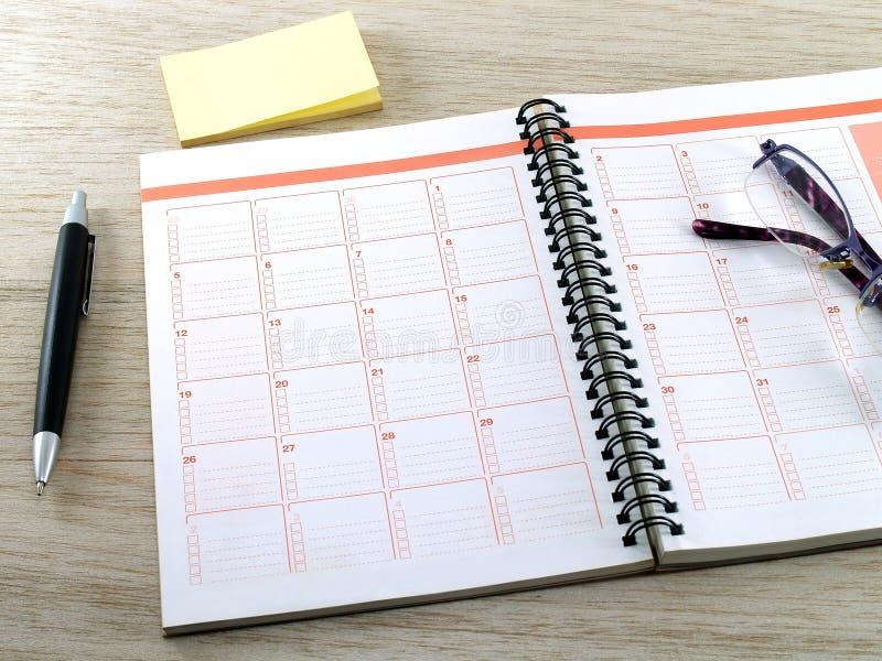 Anteckningsbok, glasögon, penna och tomma klibbiga anmärkningar för guling på trätabellgolv royaltyfria bilder