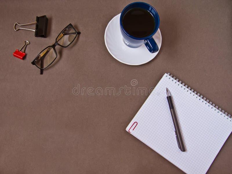 Anteckningsbok kaffekopp, exponeringsglas, kontorstillf?rsel royaltyfri bild