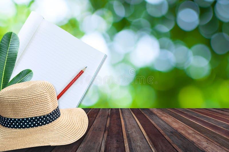 Anteckningsbok med blyertspenna- och sugrörhatten på trätabellen med grön bokeh royaltyfri foto
