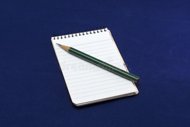 Anteckningsbok med den gröna blyertspennan royaltyfri fotografi
