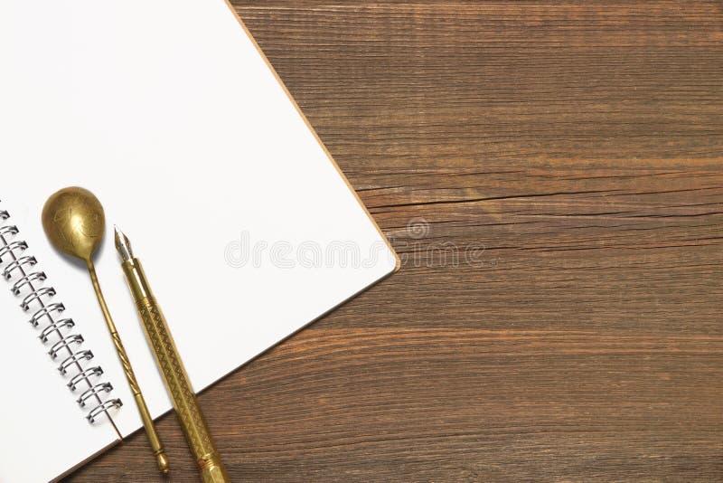 Anteckningsbok med den tomma sidan, skeden och Pen On Wood Table royaltyfri foto