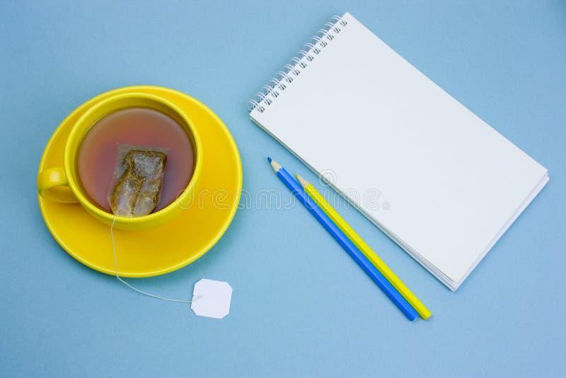anteckningsbok med det tomma vita arket, blyertspennor och kopp te royaltyfri fotografi