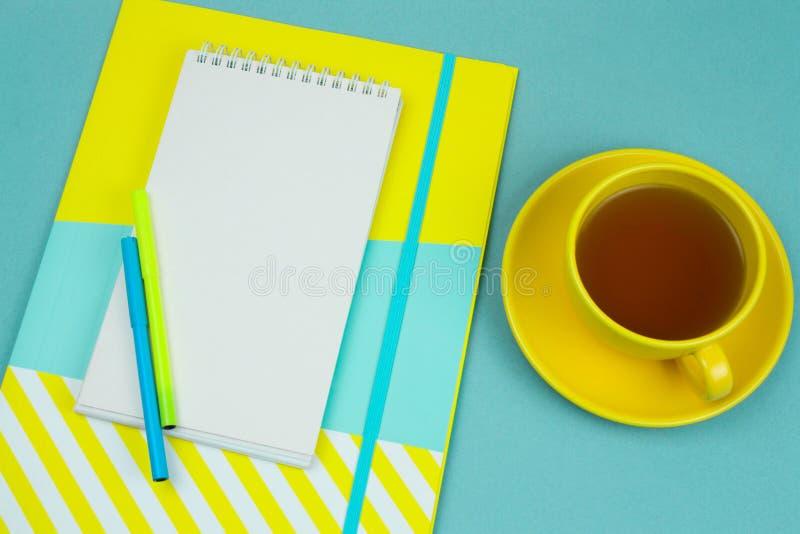 anteckningsbok med det tomma vitbokarket, pencilsandkopp te på en blå bakgrund royaltyfri fotografi