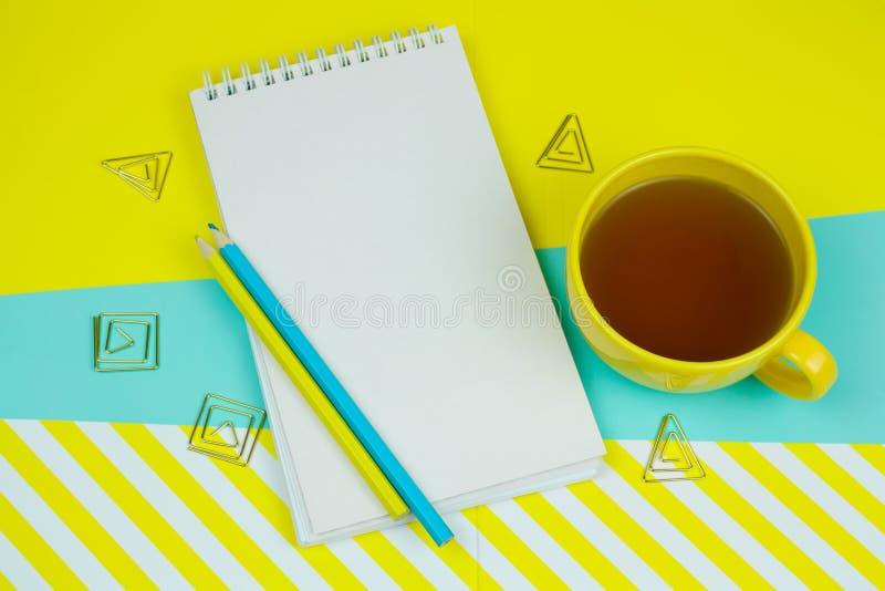 anteckningsbok med det tomma vitbokarket, pencilsandkopp te på en blått och gul moderiktig vibrerande bakgrund royaltyfri fotografi