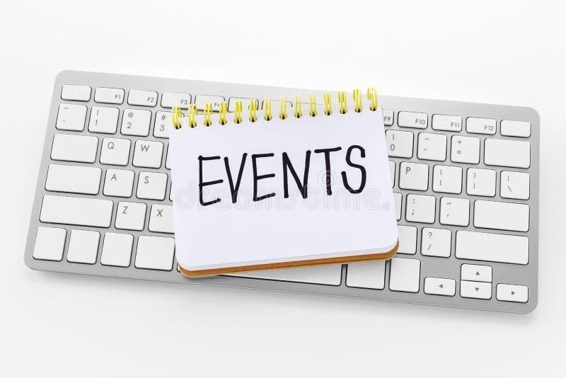 Anteckningsbok med händelseord på tangentbordet fotografering för bildbyråer