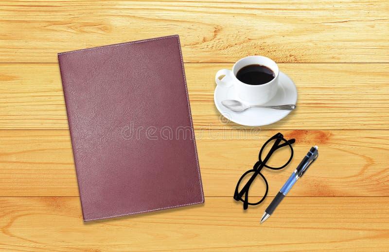 Anteckningsbok med kontorstillförsel med pennan med exponeringsglas och koppen royaltyfria bilder