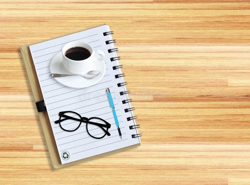 Anteckningsbok med kontorstillförsel med pennan med exponeringsglas och koppen av c royaltyfri fotografi