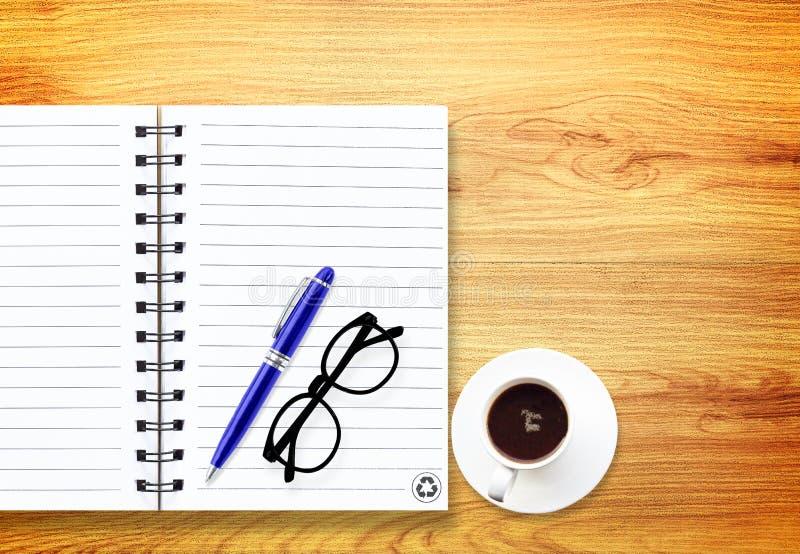 Anteckningsbok med kontorstillförsel med pennan med exponeringsglas och koppen av c royaltyfri bild