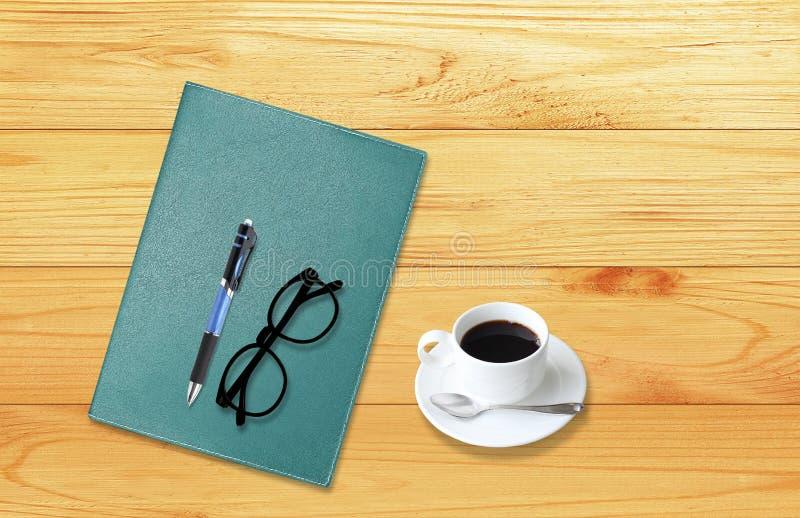 Anteckningsbok med kontorstillförsel med pennan med exponeringsglas och koppen av c arkivbilder