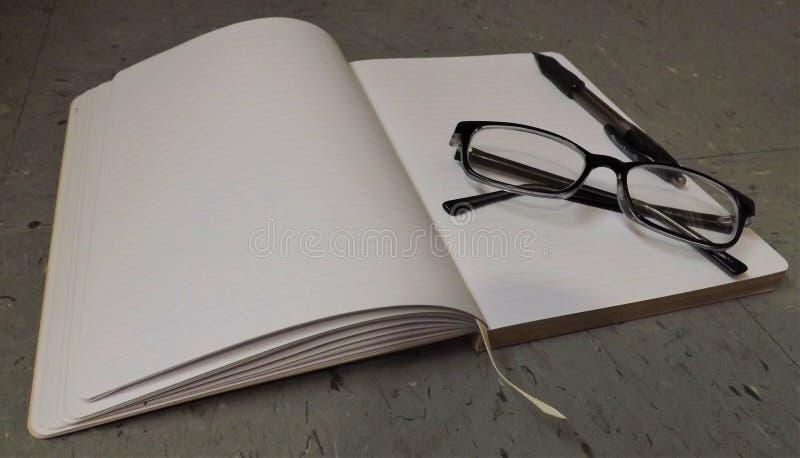 Anteckningsbok med läs- exponeringsglas och pennan överst arkivfoton
