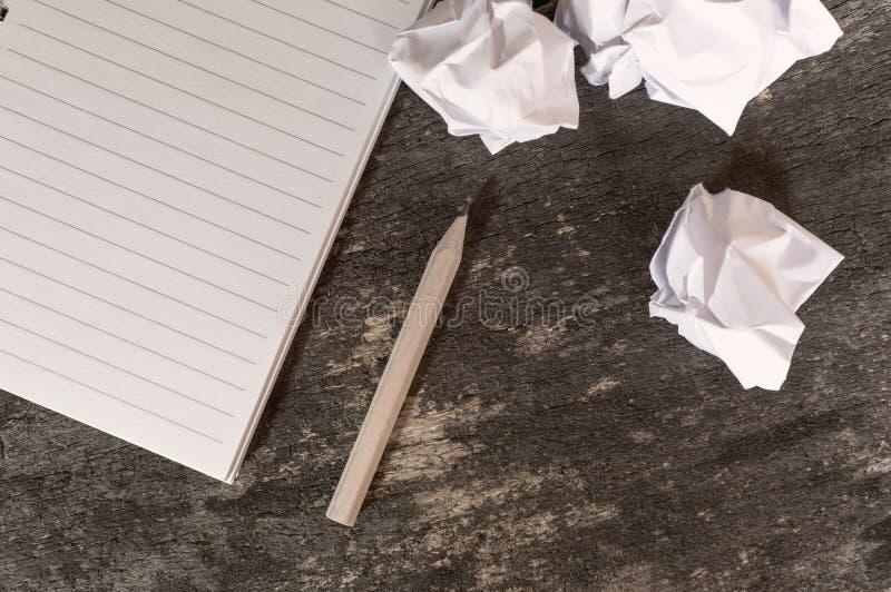 Anteckningsbok med pennan och skrynkligt papper på trätabellen royaltyfri fotografi