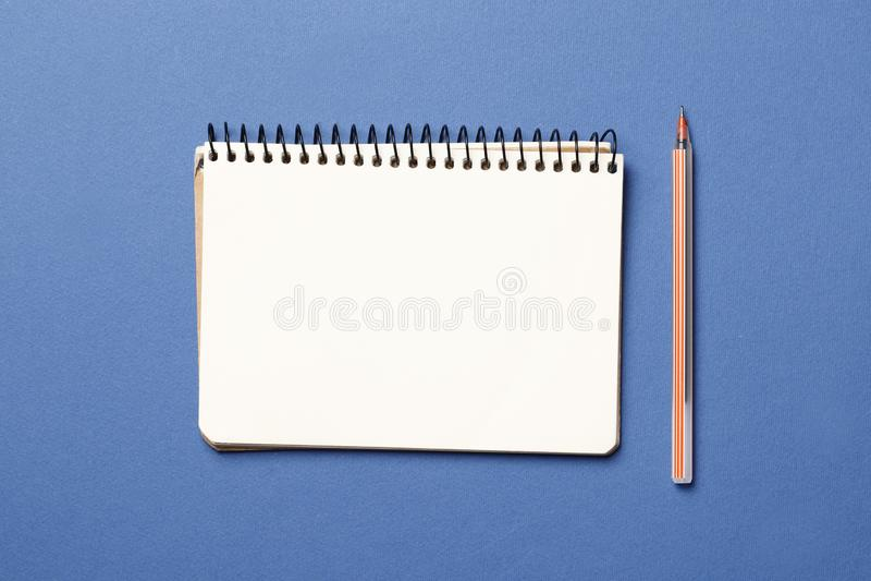 Anteckningsbok med pennan på blå bakgrund fotografering för bildbyråer