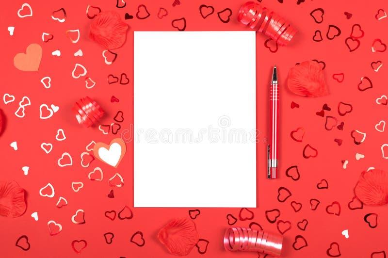 Anteckningsbok med pennan på röd bakgrund med hjärta-formade konfettier royaltyfri fotografi
