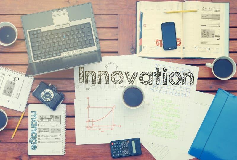 Anteckningsbok med text inom innovation på tabellen med kaffe, några royaltyfria foton