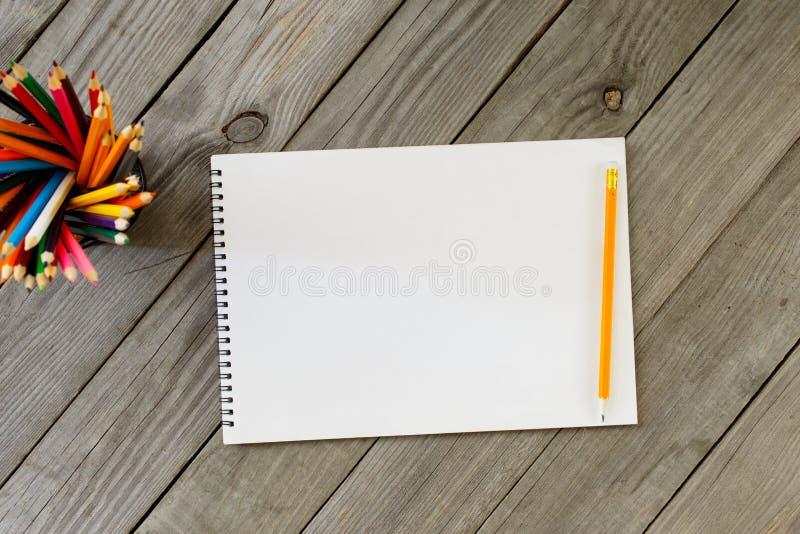 Anteckningsbok med tomma sidor och färgade blyertspennor arkivfoton