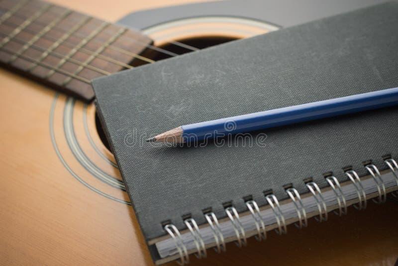 Anteckningsbok och blyertspenna på gitarren royaltyfri fotografi
