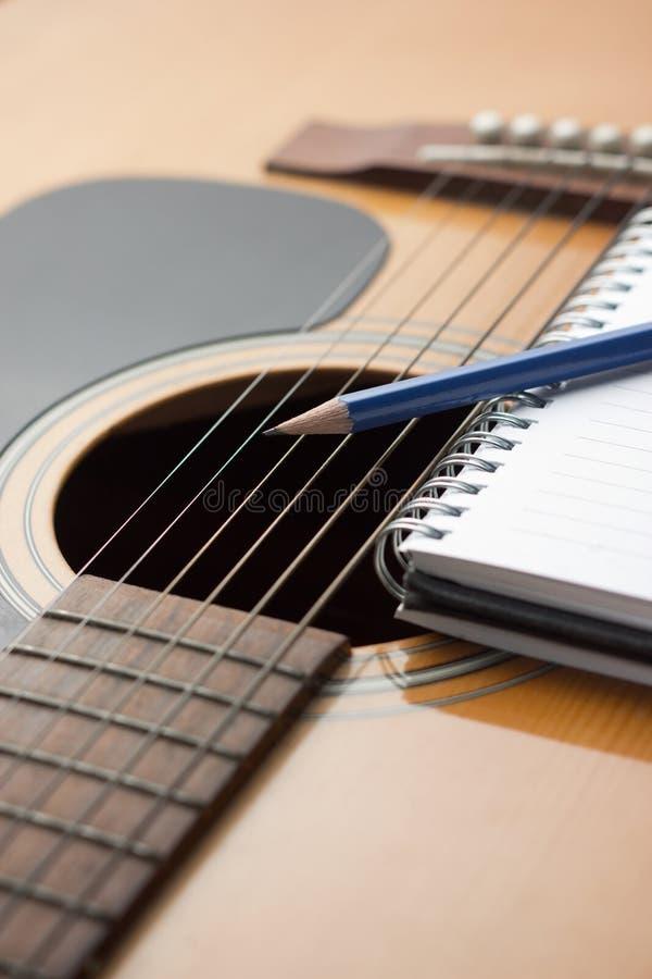 Anteckningsbok och blyertspenna på gitarren arkivfoto