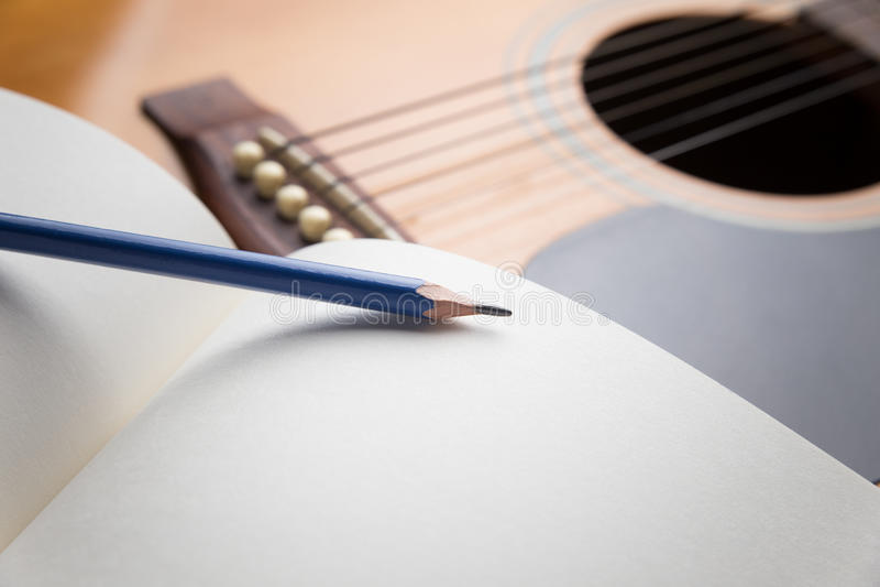 Anteckningsbok och blyertspenna på gitarren royaltyfria foton