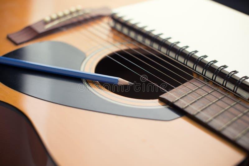 Anteckningsbok och blyertspenna på gitarren som skriver musik royaltyfri bild