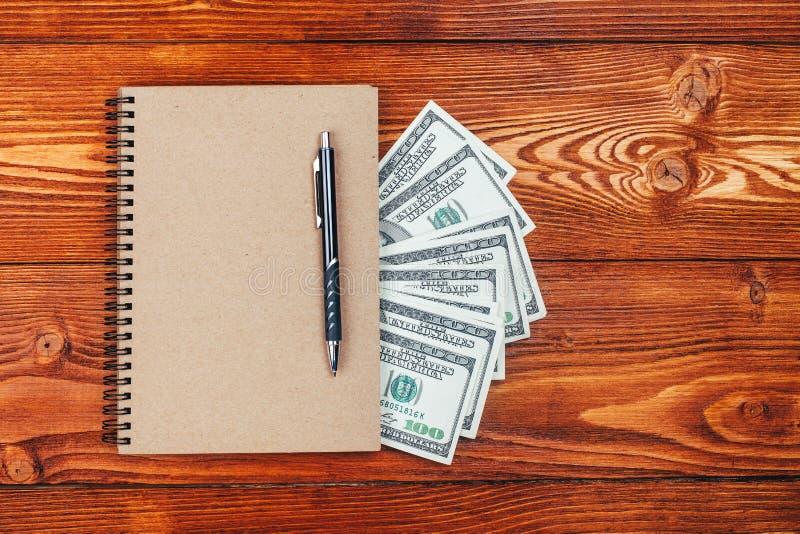 Anteckningsbok och dollar royaltyfri bild