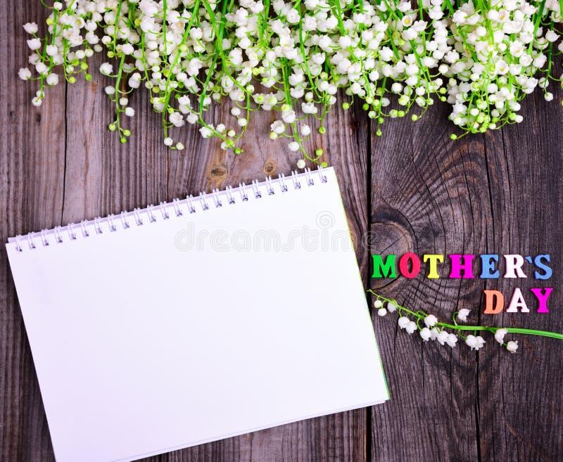 Anteckningsbok och en lyckönsknings- inskrift med en dag för moder` s royaltyfria foton
