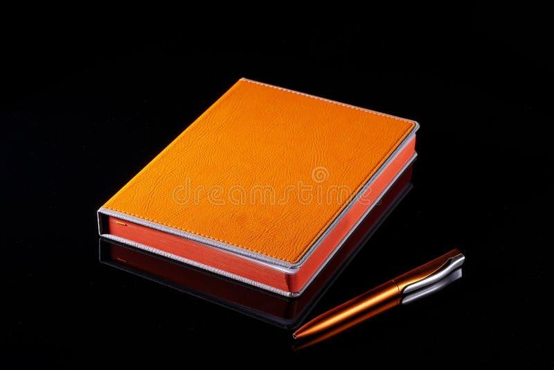Anteckningsbok och ljus apelsin för penna på en svart bakgrund arkivbild