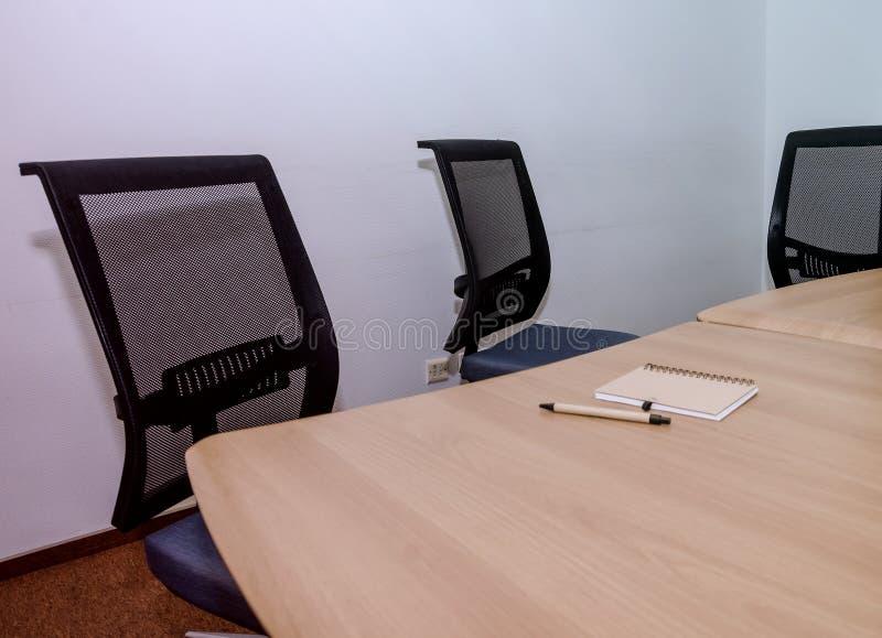 Anteckningsbok och penna på ett kontorsskrivbord Tabell och stolar i kontoret Konferensrum i kontoret arkivbild