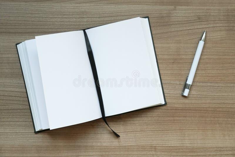 Anteckningsbok och penna på skrivbordet arkivbilder