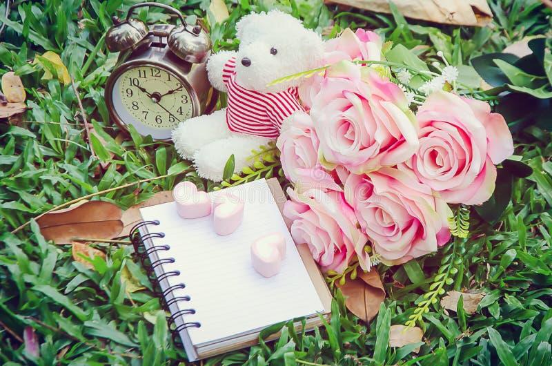 Anteckningsbok- och rosa färghjärtamarshmallowerna och den vit nallebjörnen och tappning tar tid på och buketten av rosa färgrose royaltyfri bild