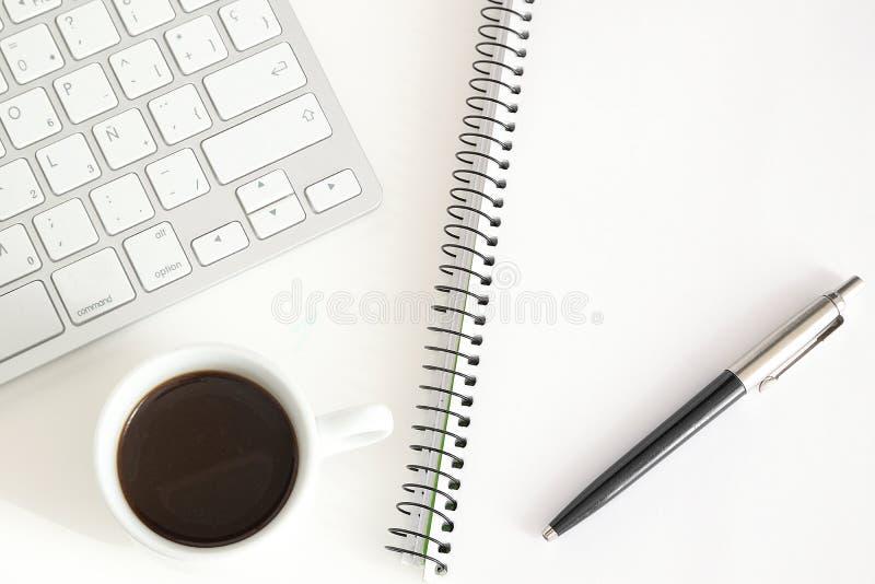 Anteckningsbok och tangentbord bredvid en kopp kaffe på ett vitt skrivbord Begrepp för hem- arbete arkivfoton