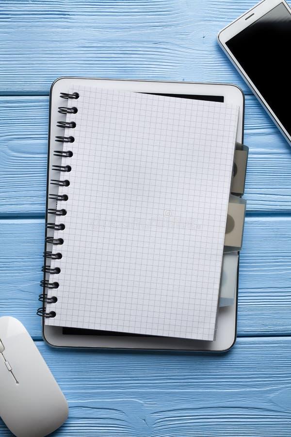 Anteckningsbok på den digitala minnestavlan, den vita smartphonen och datormus arkivfoton