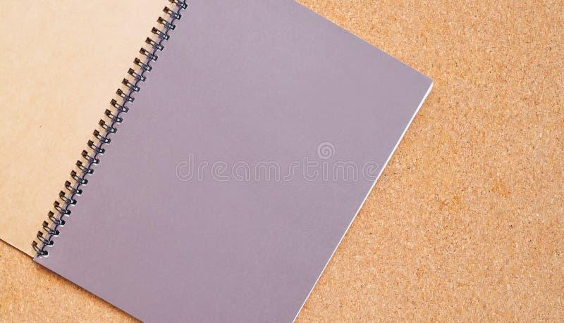Anteckningsbok på ett brunt bräde med kopieringsutrymme för text royaltyfria foton