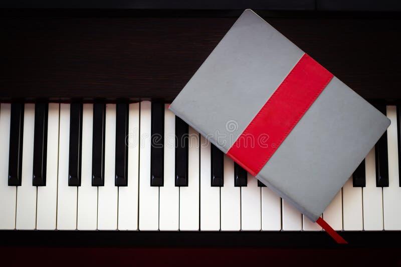 Anteckningsbok på pianotangent B?sta sikt med kopieringsutrymme arkivbild