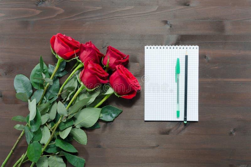 Anteckningsbok, pennor och röda rosor arkivbilder