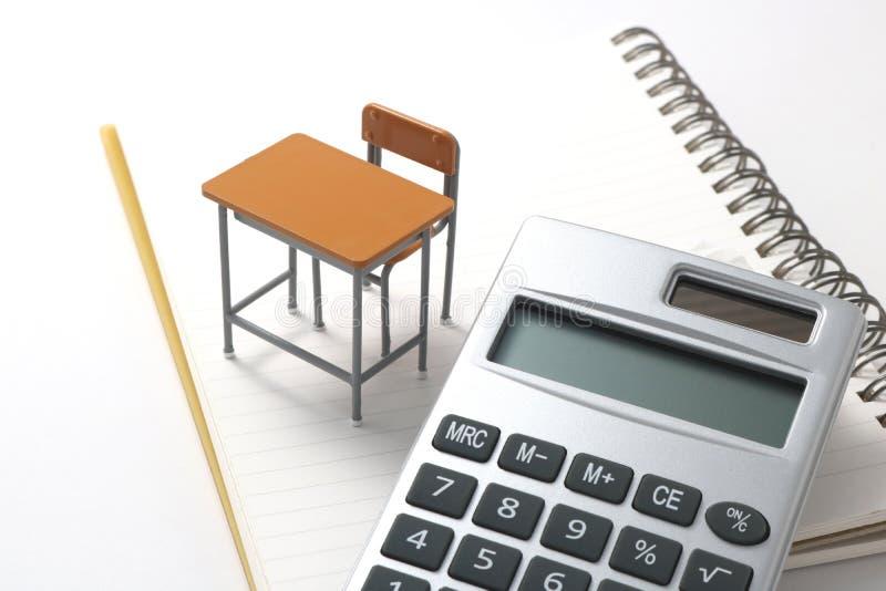 Anteckningsbok-, räknemaskin-, blyertspenna- och miniatyrskrivbord royaltyfria foton