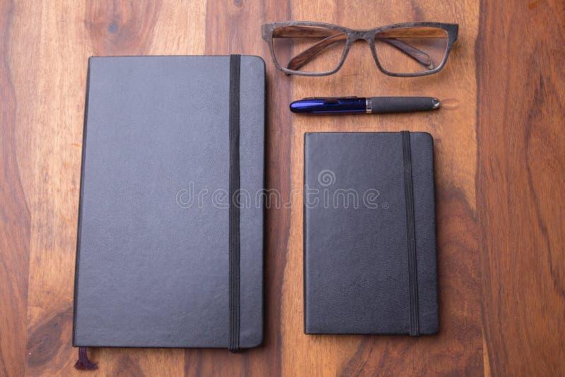Anteckningsbok två på en trätabell med träexponeringsglas och en penna fotografering för bildbyråer