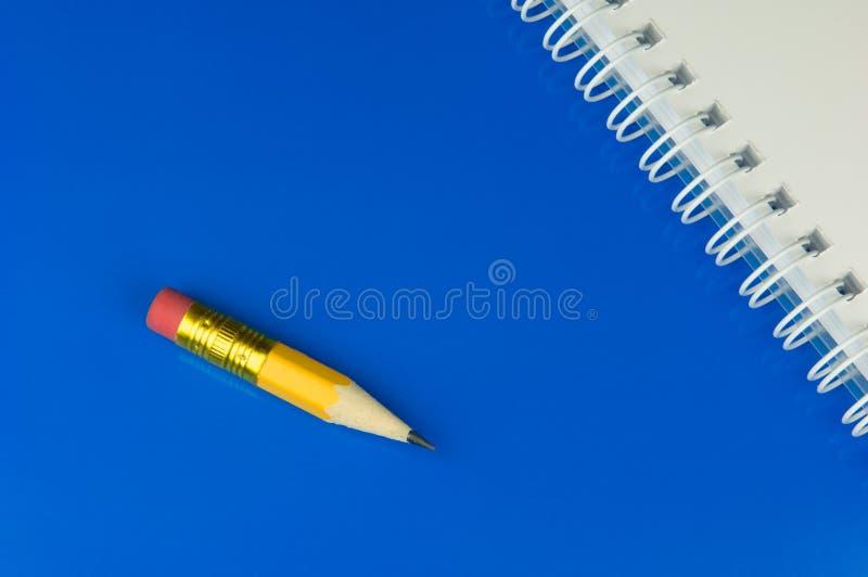anteckningsbokblyertspennakortslutning arkivfoto