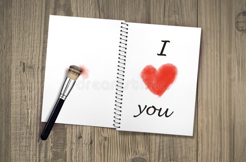 Anteckningsboken öppnade på gammal tappning som trätabellen med mig älskar dig som är handskriven, och röd hjärtaform målade med  royaltyfria bilder