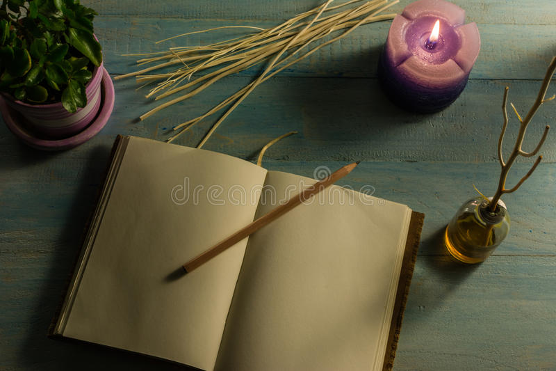 Anteckningsboken blyertspenna, vädrade stearinljus, nödvändiga oljor, trädfilialer, små träd i krukor På en trätabell arkivbilder