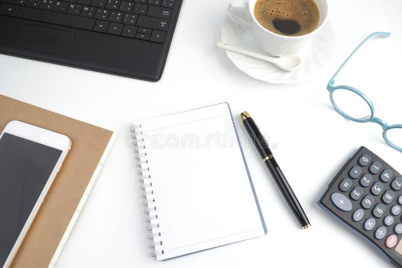 Anteckningsboken för tom sida på det vita skrivbordet med pennan, kaffe, lapto royaltyfria bilder