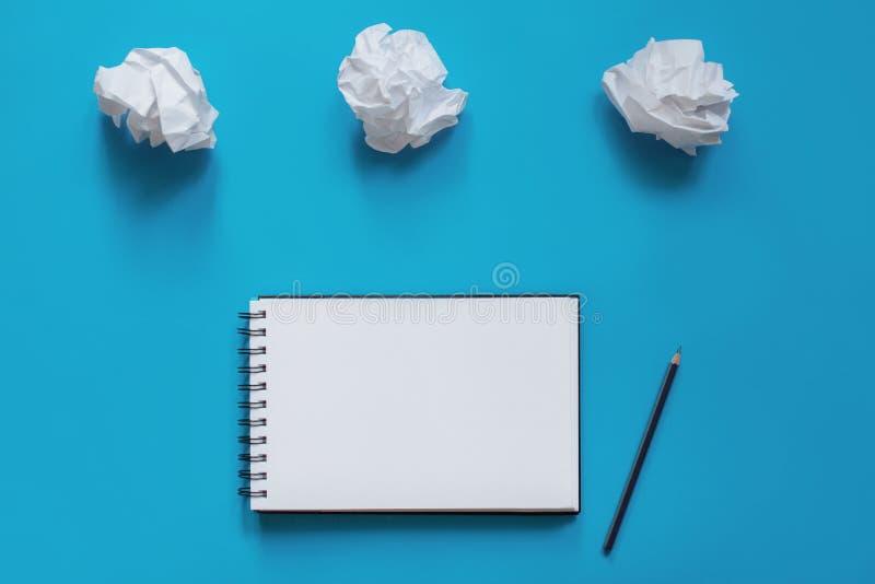 Anteckningsboken med en blyertspenna och klumpa sig av papper royaltyfri bild
